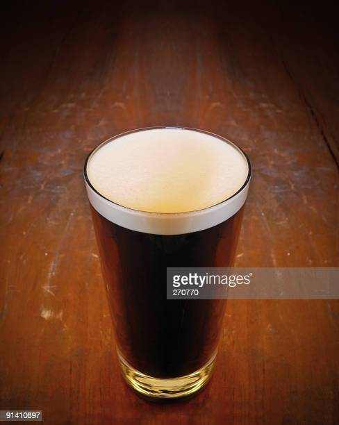 Pint Of Stout beer on wooden bar counter