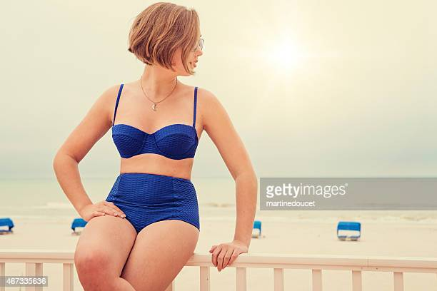 Pin-up girl in fifties style bikini, vintage look at beach.