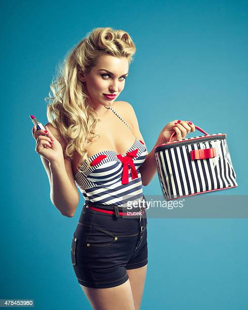 Pin-up style sailor blonde woman holding lipstick