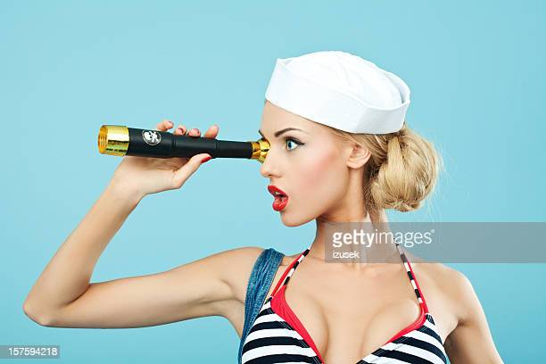 Pin-up style sailor woman looking through telescope