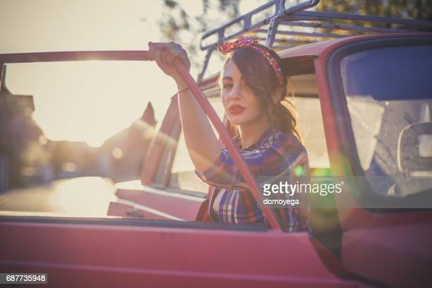 Pin-up woman and vintage car on a beautiful sunny day