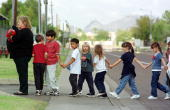 Pioneer Elementary School children are led off a bus after they were evacuated from their school following a hostage taking 24 October in Glendale...