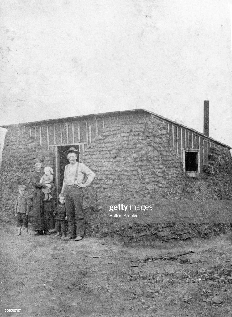 A pioneer family poses for a portrait outside their mudbrick habitat on the Great Plains in the Dakota Territory late 20th Century