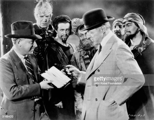 Pioneer Hollywood directors Cecil B DeMille and D W Griffith on the set of a biblical epic Griffith appears to be about to sign an autograph for...