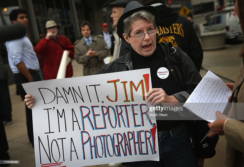 Pioneer Press reporter Kathy Routliffe joins other demonstrators including union members, reporters, and photographers march outside the offices of the Chicago Sun-Times protesting the newspapers decision to eliminate its 28-member photography staff on June 6, 2013 in Chicago, Illinois. The newspaper chain plans to train their reporters to take pictures with iPhones to fill the void.