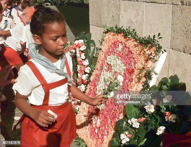 A pioneer puts a flower on the image of Cuban revolutionary Ernesto 'Che' Guevara on the 31st anniversary of his death Una pionera pone flores...