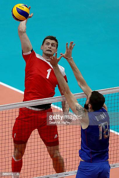 Piotr Nowakowski of Poland spikes past Alexander Volkov of Russia during a Men's Preliminary Pool B match on Day 8 of the Rio 2016 Olympic Games at...