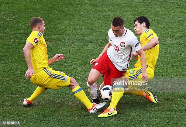 Piotr Zielinski of Poland is tackled by Olexandr Kucher of Ukraine and Taras Stepanenko of Ukraine during the UEFA EURO 2016 Group C match between...