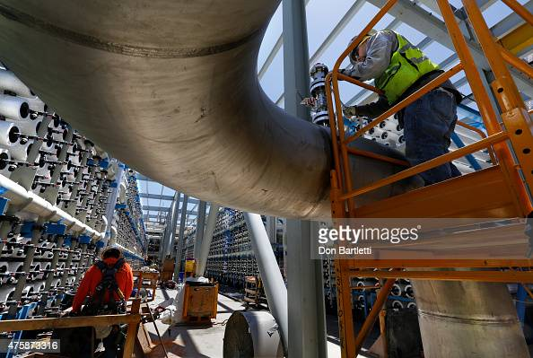 Pipe fitter Steven Montes installs a pressure relief valve on a 24' stainless steel pipe at the Poseidon Water desalination plant April 30 2015 in...