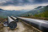Dark clouds over pipeline construction in hilly landscape, Slovenia, Europe.