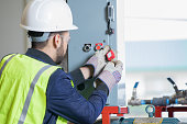 Young adult Hispanic man is engineer or inspector on pipeline oil and gas job site. Man is using a lock and key to lock breaker box and observe safety protocols.