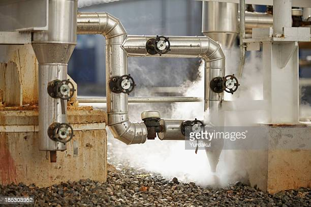 pipelines emitting steam at industrial site