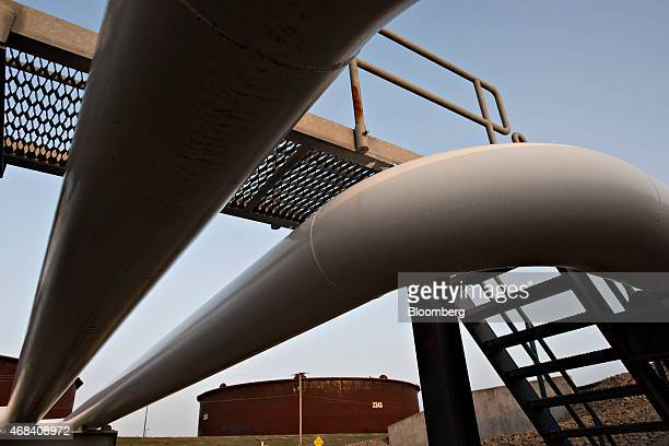 Pipelines run toward oil storage tanks stand at the Enbridge Inc Cushing storage terminal in Cushing Oklahoma US on Wednesday March 25 2015 The...