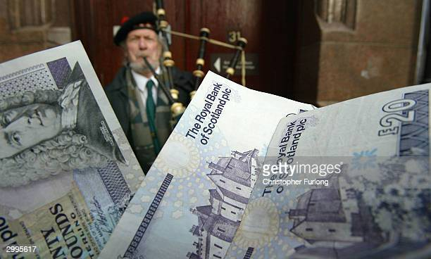 A piper entertains tourists outside The Royal Bank of Scotland's Fountain Bridge branch on February 19 2004 in Edinburgh Scotland The bank has...