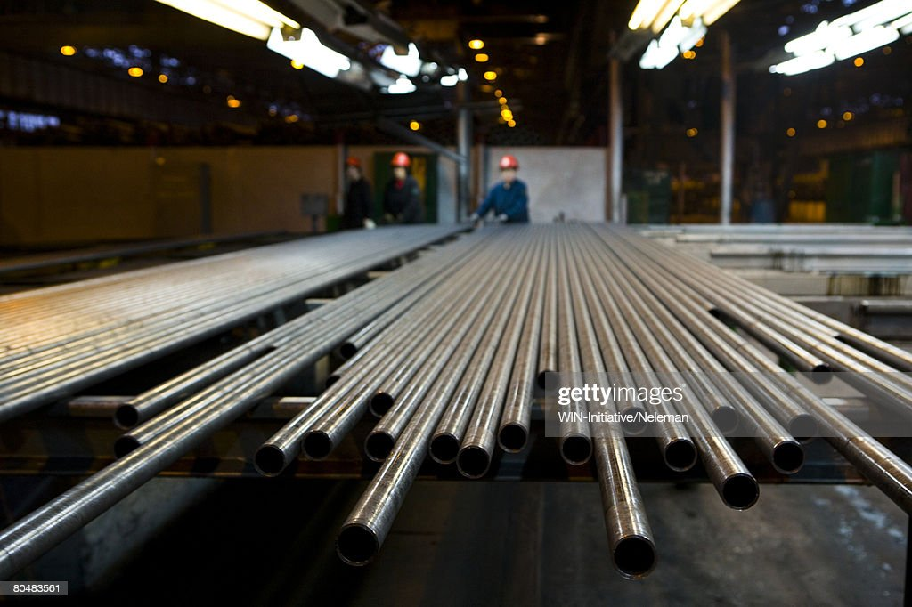 Pipes in row with workers in steel factory