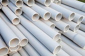 Heap of PVC pipes stacked at construction site, Close-up.