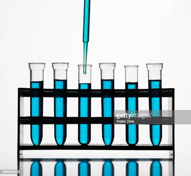 Pipette dripping blue liquid into test tubes