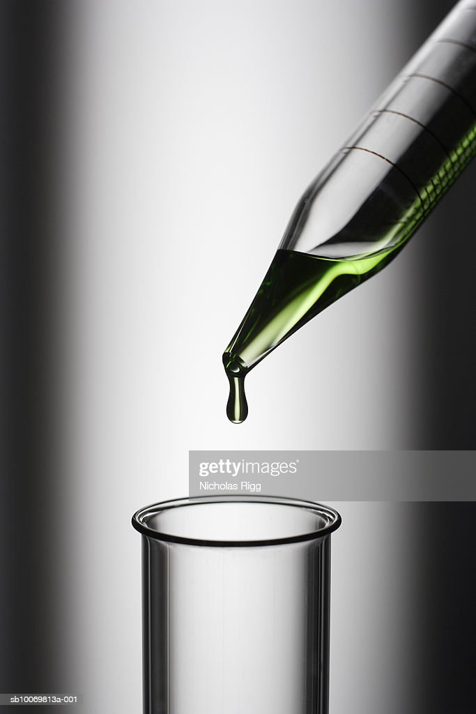 Pipette with green liquid and test tube, studio shot