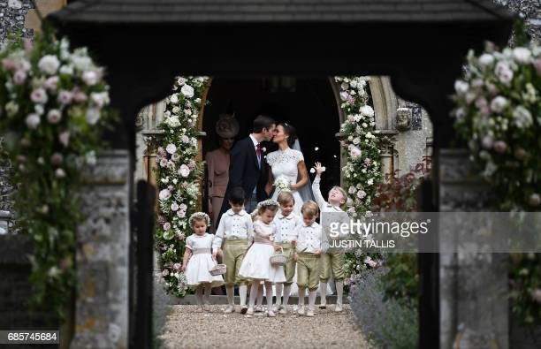 Pippa Middleton kisses her new husband James Matthews following their wedding ceremony at St Mark's Church in Englefield west of London on May 20 as...