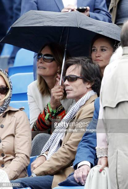 Pippa Middleton shelters underneath an umbrella with her mum Carol during the match between JoWilfried Tsonga and Igor Sijsling at the AEGON...