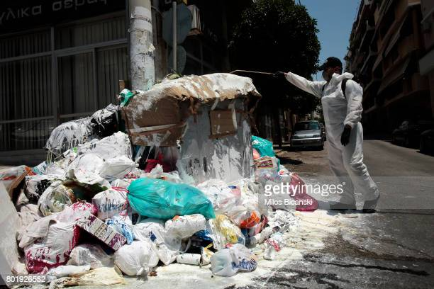 Piraeus city hall has hired a private companies to spray hills of garbage with a calx as mounds of rubbish festered in soaring temperatures in Athens...