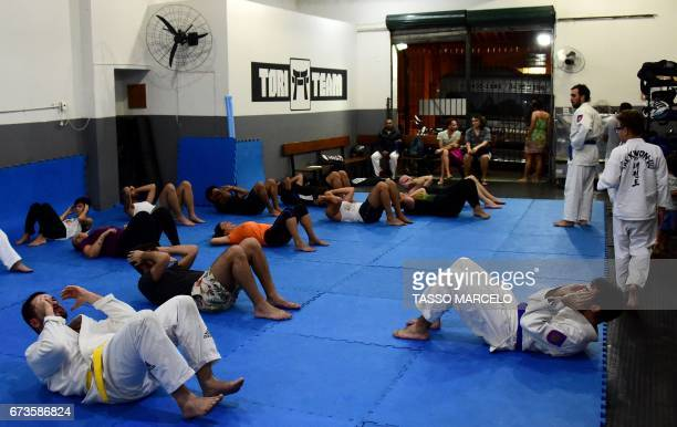 CORRECTION 'Piranha Team' members warm up before taking a krav maga selfdefence technique class in Rio de Janeiro Brazil on April 18 2017 A group of...