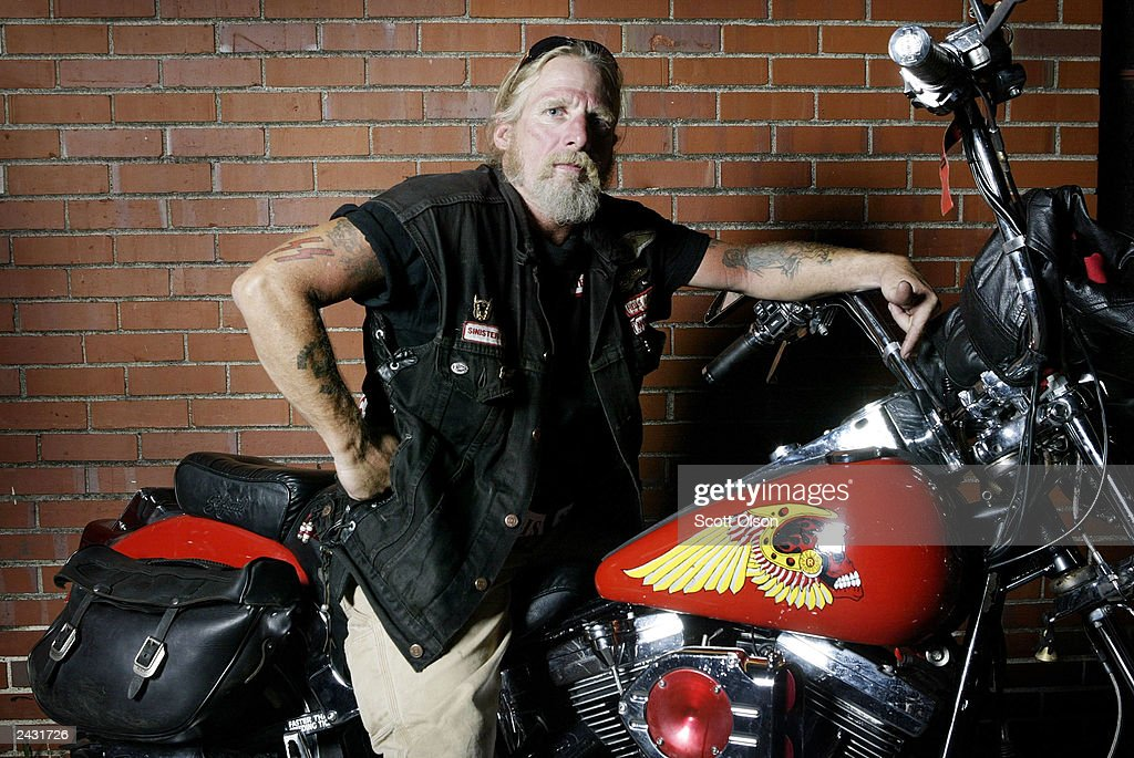 Pirate, a member of the Illinois Nomads charter of the Hells Angels motorcycle club, sits on his motorcycle outside a party hosted by the Midwest Percenters motorcycle club August 23, 2003 in Quincy, Illinois. The Hells Angel's flaming skull logo is painted on the gas tank.