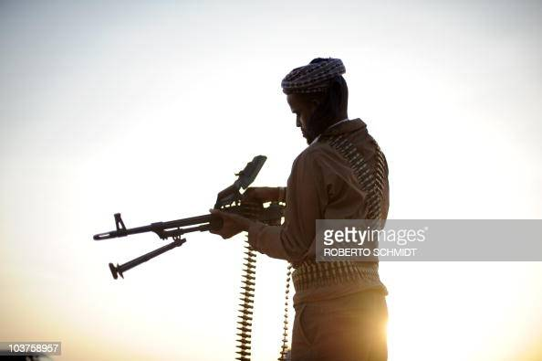 A pirate loads his high caliber weapon in the early morning in the semidesertic plains near the central Somalia town of Galkayo on August18 2010...