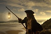Pirate on a beach with lantern at sunset.He is wearing a Tricorn hat, frayed white shirt and  gold braided long black trench coat. Model is holding the lantern up as if signalling ships, to lure them