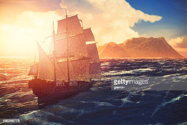 Pirate ship sailing towards lonely island at sunset