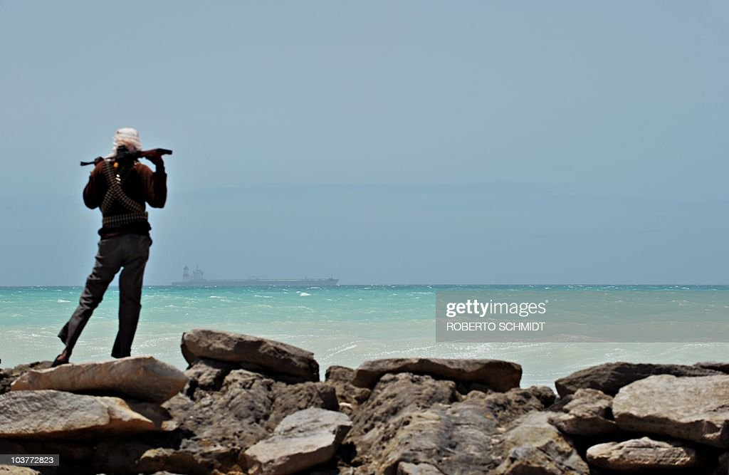 A pirate stands on a rocky outcrop on the coast in Hobyo, central Somalia, on August 20, 2010 as he looks at a hijacked Korean supertanker anchored on the horizon. The Marshall Islands-flagged VLCC Samho Dream is a third of a kilometre long, one of three largest vessels ever hijacked by pirates, and carries an estimated 170 million dollars of Iraqi oil destined for the United States. Fighting a losing battle against the sand that has already completely covered the old Italian port, Hobyo's scattering of rundown houses and shacks looks anything but the nerve centre of an activity threatening global shipping. Hobyo pirates have collected millions of dollars in ransoms over the past two years. They even have currency checking and counting machines for the bags of air-dropped cash they receive.