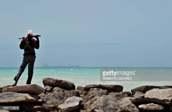 A pirate stands on a rocky outcrop on the coast in Hobyo central Somalia on August 20 2010 as he looks at a hijacked Korean supertanker anchored on...