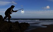 Pirate on a beach with lantern at dusk.He is wearing a Tricorn hat, frayed white shirt and  gold braided long black trench coat. Model is holding the lantern up as if signalling ships, to lure them in