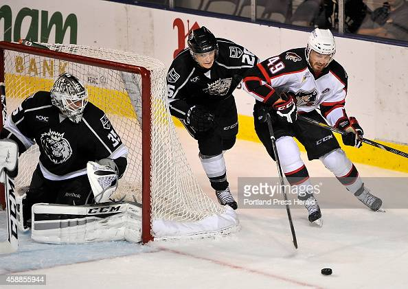 Pirates Alex Bolduc controls the puck behind the Monarch goal being chased by Monarch Nic Dowd as the Portland Pirates host the Manchester Monarchs...