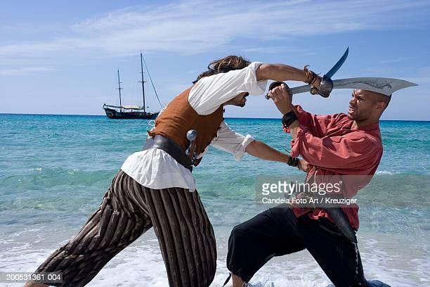 Pirates involved in swordfight on beach