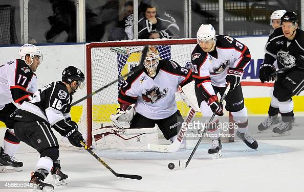Pirates Mark Louise takes the puck out after a shot on goal as Monarch Sean Backman looks to stop him as the Portland Pirates host the Manchester...