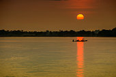 Silhouette of a typical pirogue (dugout canoe) at sunset at Congo river.
