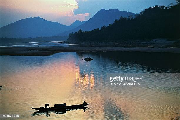 Pirogue on the Mekong River at sunset Laos