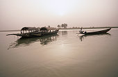 Pirogues on the Niger river at Mopti. Visitors can hire these dugout canoes for guided scenic trips, with dusk being a recommended time.
