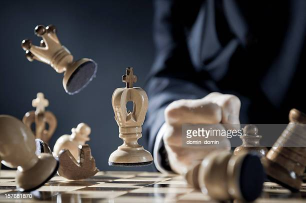 Pissed off chess player is punching in the chessboard