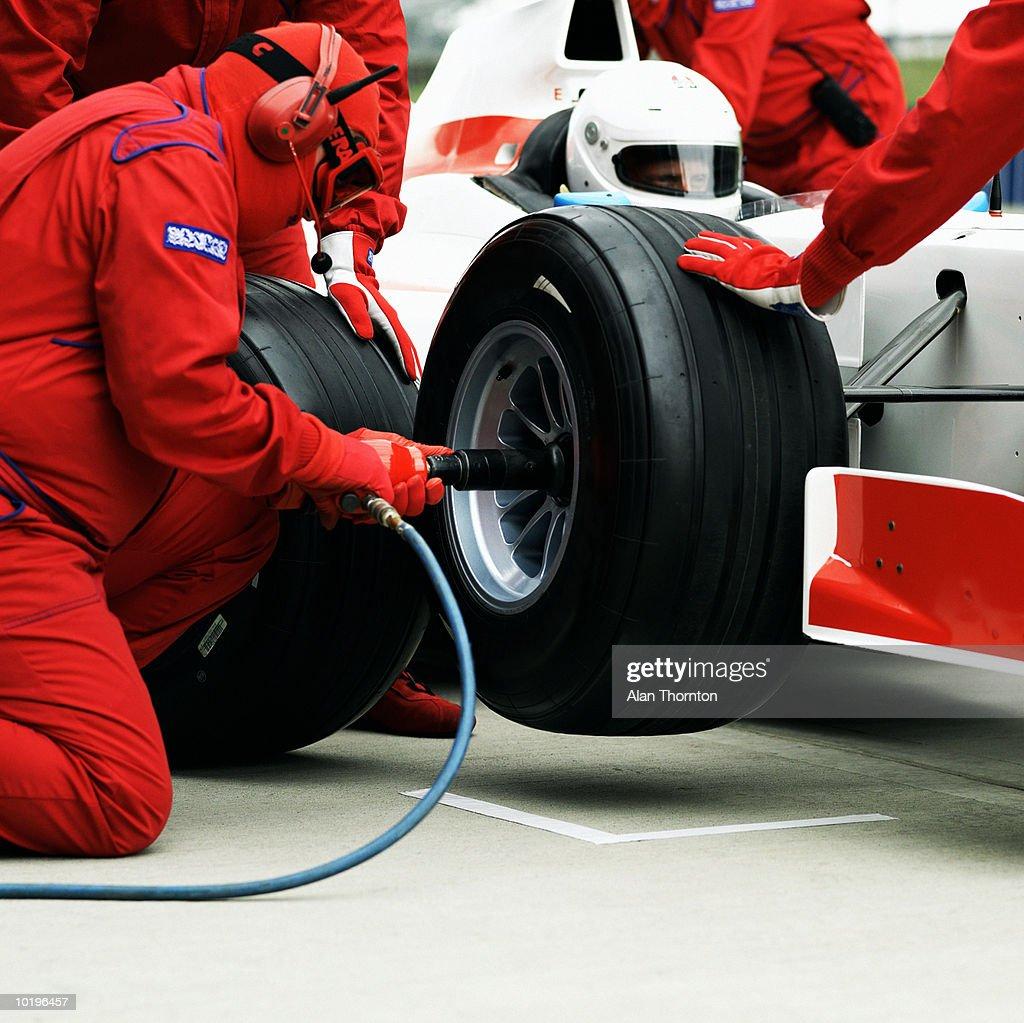Pit crew changing racing car wheel : Stock Photo