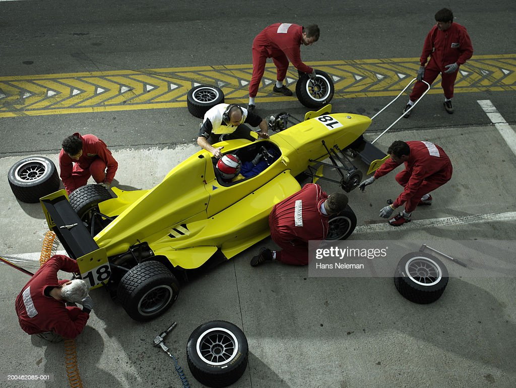 Pit crew changing tires on Formula 1 race car, elevated view : Stock Photo