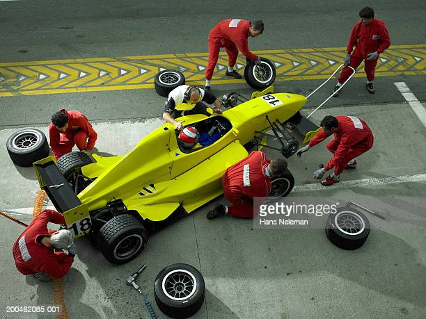 Pit crew changing tires on Formula 1 race car, elevated view
