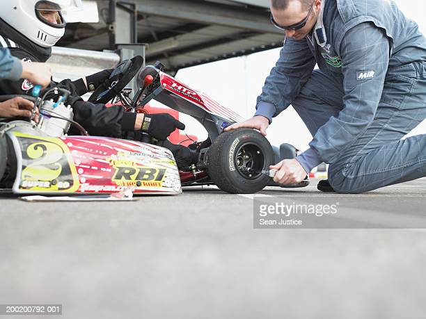 Pit crew member adjusting tire on go-cart, side view