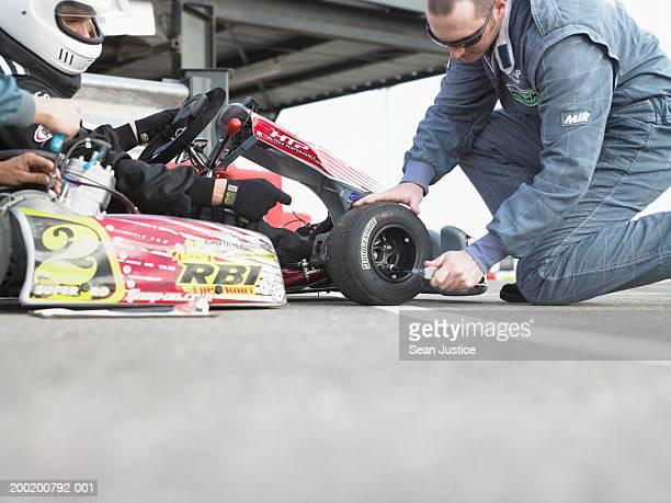Pit crew member adjusting tire on go-cart, side view