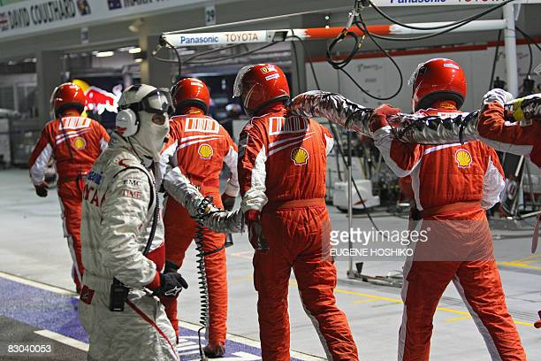 Pit crew members of Brazilian driver Felipe Massa of Ferrari carry back the fuel hose after Massa drove off with it attached during the final of...