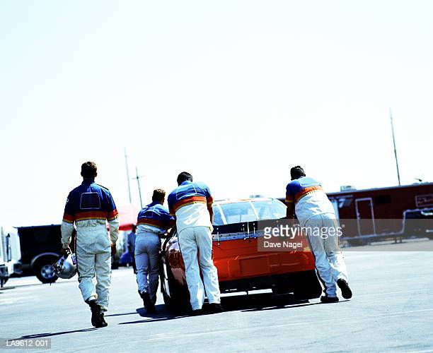 Pit crew pushing racing car, rear view