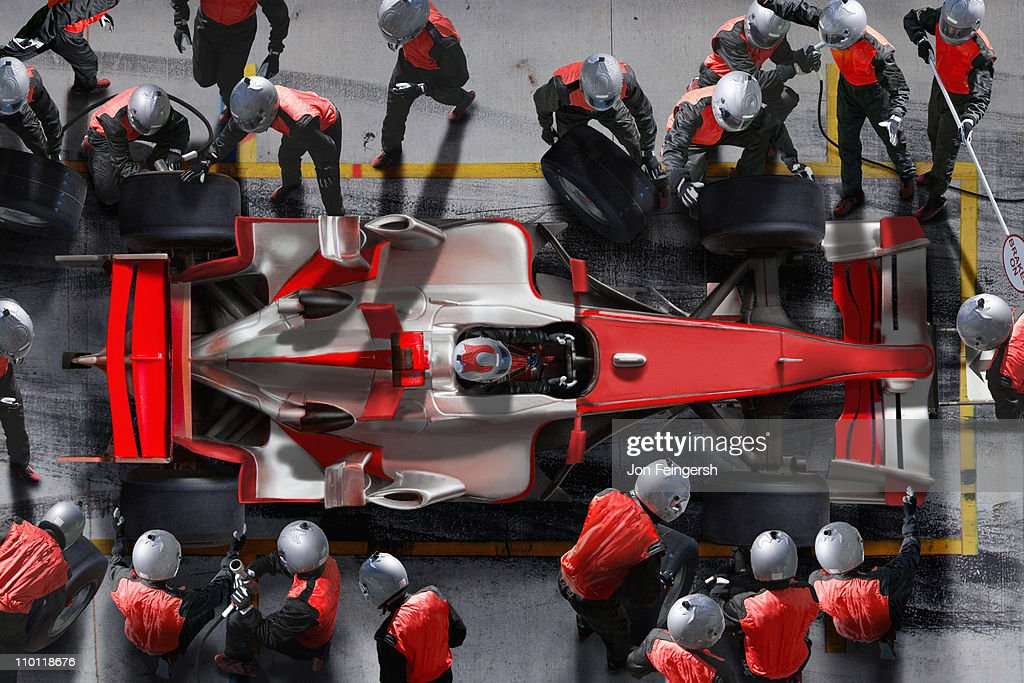 F1 pit crew working on F1 car. : Stock Photo