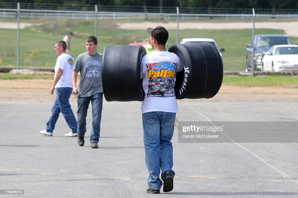 Pit crews carry tires and prepare cars prior to the Budweiser King of Beers 150 at Thompson Speedway August 15, 2013 in Thompson, Connecticut.