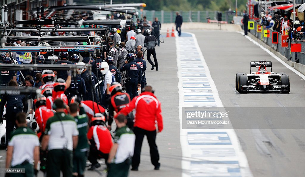 Pit crews gather in the pit lane as Jules Bianchi of France and Marussia exits the garage during practice ahead of the Belgian Grand Prix at Circuit de Spa-Francorchamps on August 22, 2014 in Spa, Belgium.